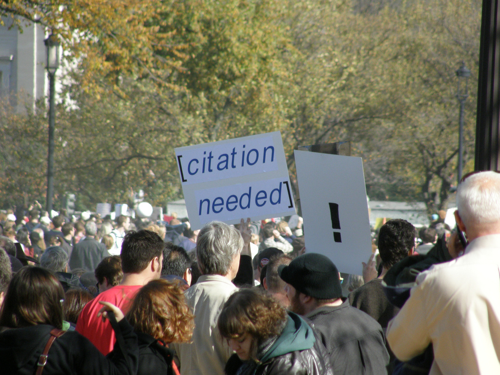 "A crowd of people with one person carrying a placard with ""!"" on it and another with ""citation needed"" on it"