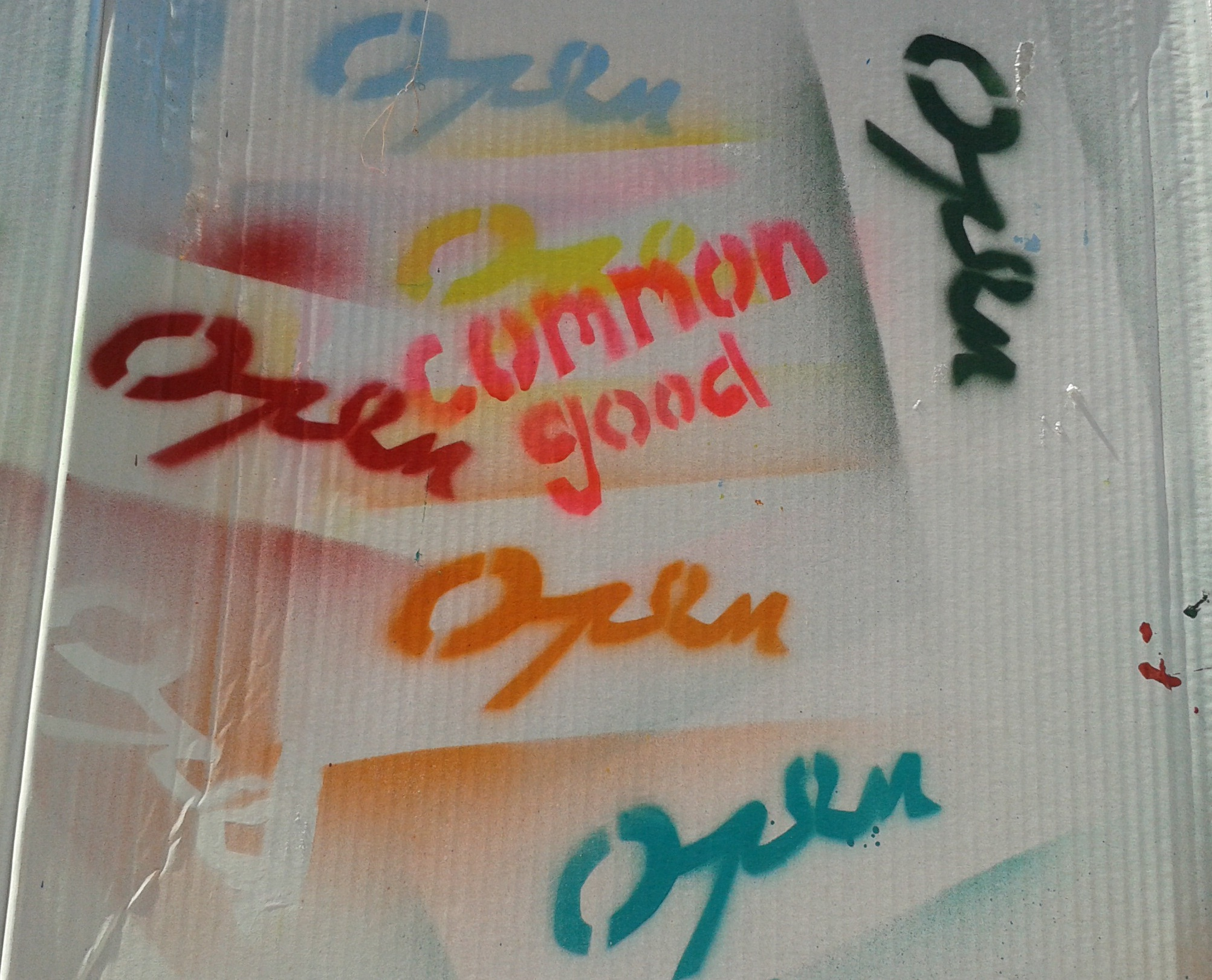 "Graffiti with words ""open"" in different colours and ""common good"" in orange"